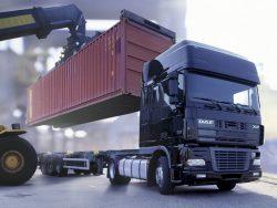 Автомобиль-контейнеровоз загружается контейнером в порту или на железнодорожной станции без применения ручного труда.