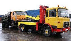 Эвакуатор с манипулятором способен поднять на платформу переднюю часть грузовика с поврежденным двигателем.