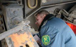Сотрудник белорусской таможни проверяет магистральную фуру.
