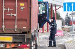 Таможенник приглашает водителя грузовика предъявить документы.