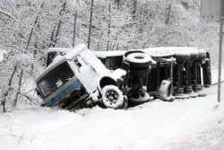 Зимняя авария грузовика на заснеженной трассе.